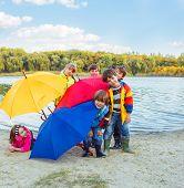 Basic school students in rainwear with umbrellas