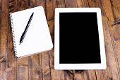 Tablet, notebook and pen on wooden background