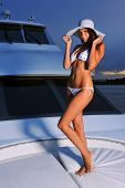 Woman with perfect slim body posing on yacht wearing bikini