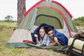Portrait of a happy young couple lying in tent on countryside landscape