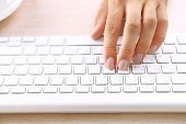 Man working with keyboard on wooden table on folders background closeup