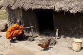 LILIIR, SOUTH SUDAN-DECEMBER 4 2010: Unidentified woman in the village of Liliir, South Sudan puts n