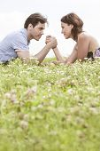 picture of wrestling  - Profile shot of couple arm wrestling while lying on grass against sky - JPG