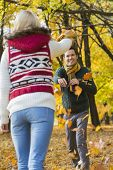 Happy young couple playing with autumn leaves in park
