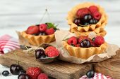 Tasty tartlets with berries on wooden table