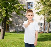 advertising, gesture, people and childhood concept - smiling little boy in white blank t-shirt point