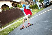 foto of skate board  - Action shot of a longboarder skating on an urban road - JPG