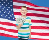 financial, planning, childhood and educational concept - smiling boy holding dollar cash money in hi