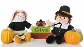 picture of give thanks  - Two happy pilgrim dolls sitting by a  - JPG