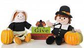Two happy pilgrim dolls sitting by a