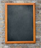 Aged blackboard hanging on brick wall as a background for your menu
