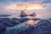 stock photo of shipwreck  - Ancient shipwrecks in the sea with sunset background - JPG