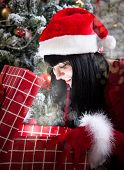 Amazed Brunette Woman Opening A Present Full Of Christmas Magic