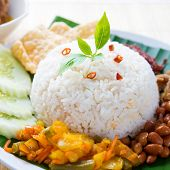 Nasi lemak kukus traditional malaysian spicy rice dish. Served with belacan, ikan bilis, acar, peanuts and cucumber.