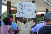 FERGUSON, MO/USA -  AUGUST 15, 2014: Man holds sign at the site of Quick Trip after Police Chief Tho