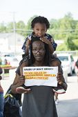 FERGUSON, MO/USA -  AUGUST 15, 2014: Man and child hold sign at the site of destroyed Quick Trip aft