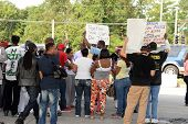 FERGUSON, MO/USA- AUGUST 15, 2014: Crown holds sign at the site of Quick Trip after Police Chief Thomas Jackson release of the name of the officer that shot Michael Brown.