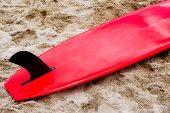 Red surfboard with black fin on sand
