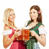 Two happy women in dirndl dress with beer in Bavaria