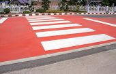 picture of zebra crossing  - white zebra crossing with red painted on asphalt street - JPG