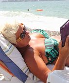 An english lady  reading her e-book