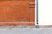 picture of downspouts  - Red brick wall of house with new metal downspout - JPG