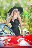 Outdoor summer portrait of stylish blonde vintage woman posing near red retro car.