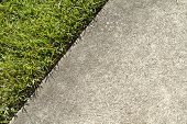stock photo of manicured lawn  - At the boundary edge where green grass in a lawn and a concrete sidewalk meet on a sunny summer day in a residential area - JPG