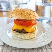 Delicious homemade hamburgers with cheese at the kitchen table.