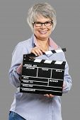 Happy elderly woman holding a clapboard, isolated on a gray background