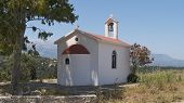 A church under a tree near Exopoli with the White Mountains beyond, Crete, Greece.