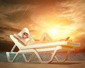 Beautiful female in white bikini near the waterpool under sun light