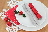 Christmas dinner place setting with white plates, red bauble decorations,cutlery, snowflakes and hol