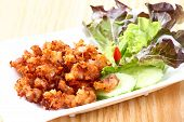 stock photo of nem  - Close up Deep fried sour fermented chicken knees tendon served with bird chili sliced cucumber and lettuce - JPG