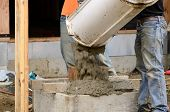 stock photo of concrete pouring  - Worker working concrete on a post fondation support at a large commercial housing development in Oregon - JPG