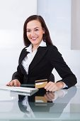 Happy Businesswoman Holding Credit Card At Desk