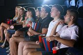 Young people watching movie in cinema