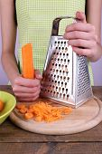 Woman grating carrot in kitchen on light background