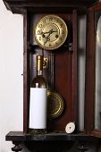 pic of pendulum clock  - Bottle of white wine with blank label template standing inside an old clock - JPG