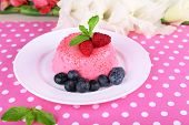 Round shaped cake with berries on plate on polka dot table cloth