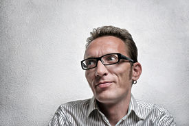 image of flirty  - Close up portrait quit satisfied man with eyeglasses looking left and up with flirty flattery smile - JPG