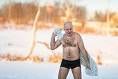 man  wipes towel after swimming in  freezing