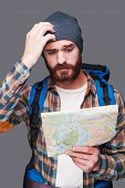 image of scratching head  - Frustrated young bearded man carrying backpack and examining map while scratching head and standing against grey background - JPG