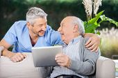 image of nursing  - Laughing male caretaker and senior man using tablet computer at nursing home porch - JPG