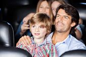 picture of watching movie  - Father and son watching film with family in movie theater - JPG