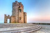 stock photo of cliffs moher  - Castle tower on Irish Cliffs of Moher at sunset - JPG