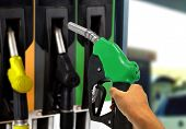 foto of gasoline station  - Hand holding Gas Nozzle at Gas Station - JPG