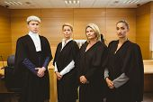 stock photo of court room  - Four serious judges standing while wearing robes in the court room - JPG