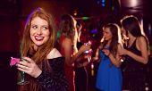 Pretty redhead drinking a cocktail at the nightclub
