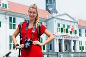 Woman tourist taking pictures of old colonial quarter in Jakarta, Indonesia